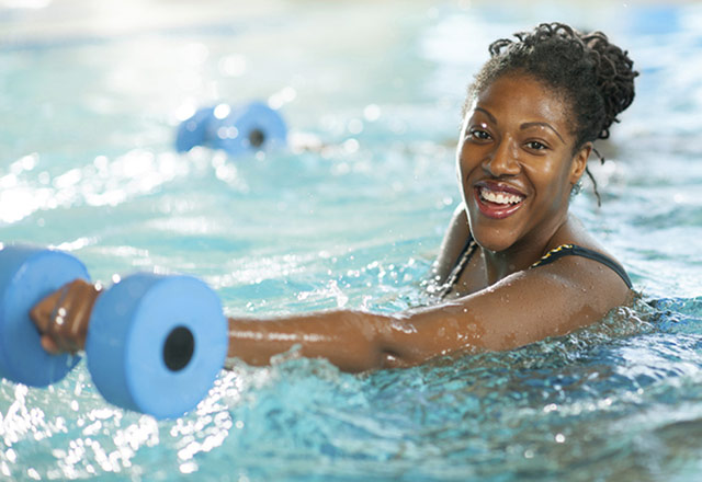 Woman lifting weights during a water aerobics class.