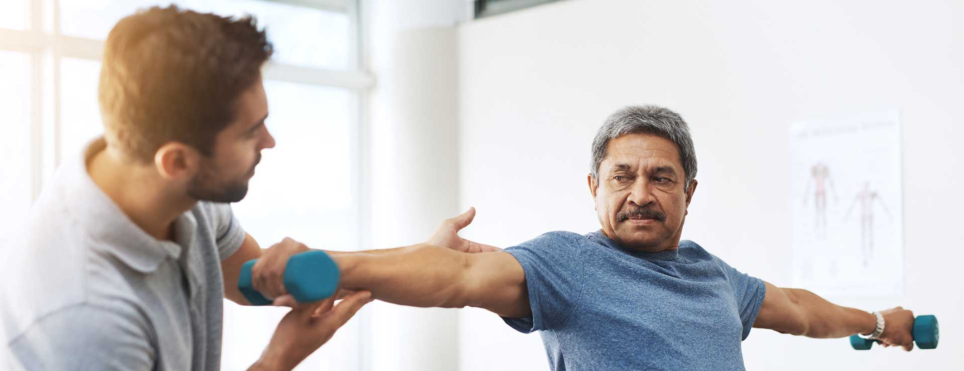 A trainer helps a man with weight training