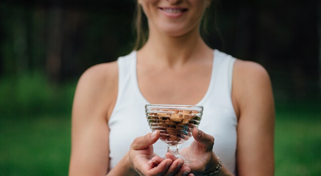 A woman holds a cup of nuts outside.