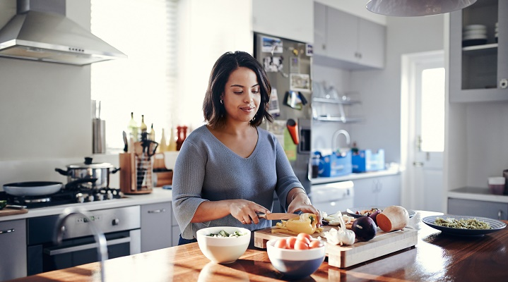 A woman cooks a healthy meal in the kitchen.
