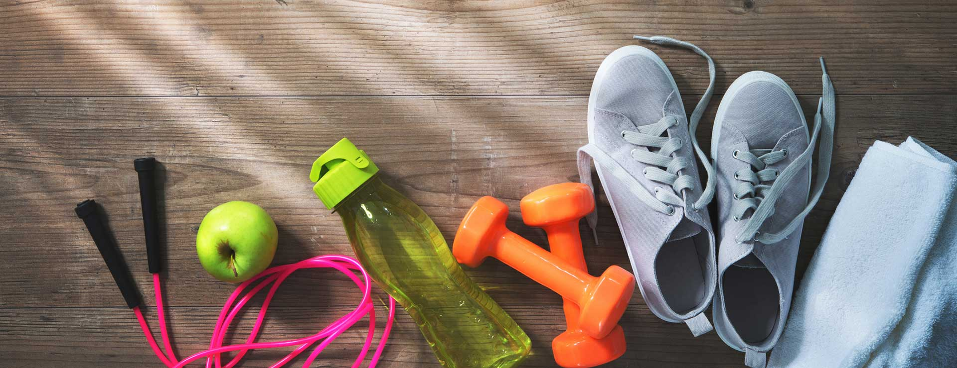 Jump rope, apple, water bottle, weights, tennis shoes and towel on the floor