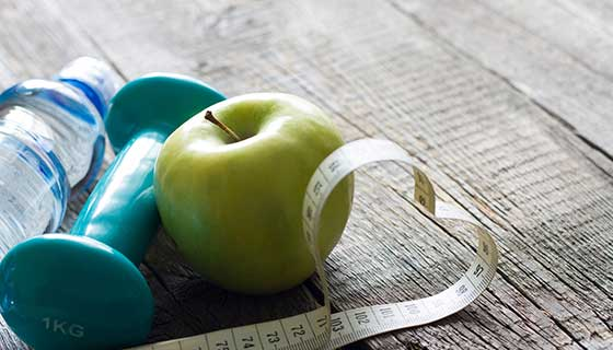 Water bottle, weight, measuring tape and apple on the floor