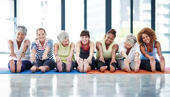 A group of women stretch before a group fitness class.