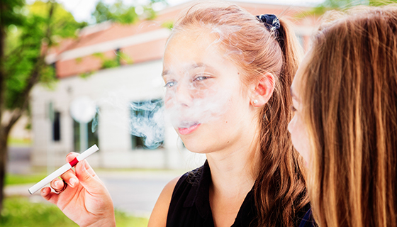 A young girl exhales from a vape pen.