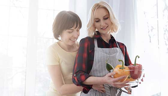 A lesbian couple cooks together.