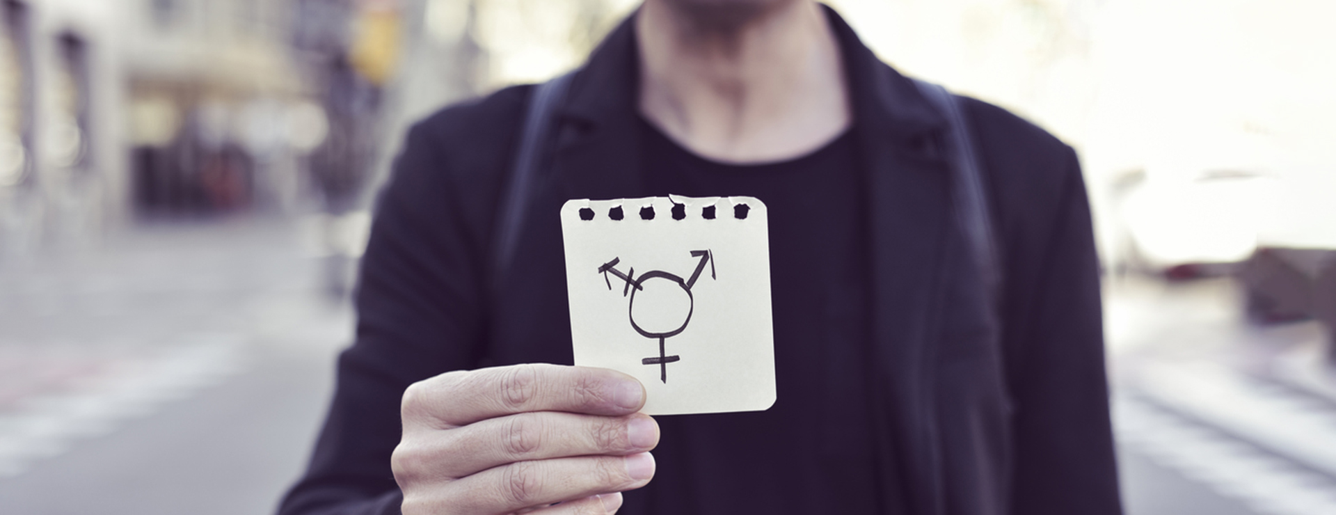 A person holds up a piece of paper with combined gender symbols.