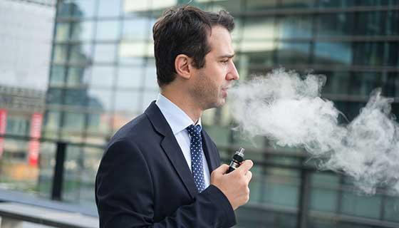A businessman vapes outdoors.
