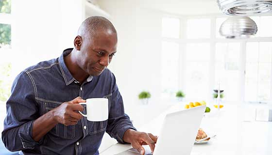 a man reading on his laptop with coffee