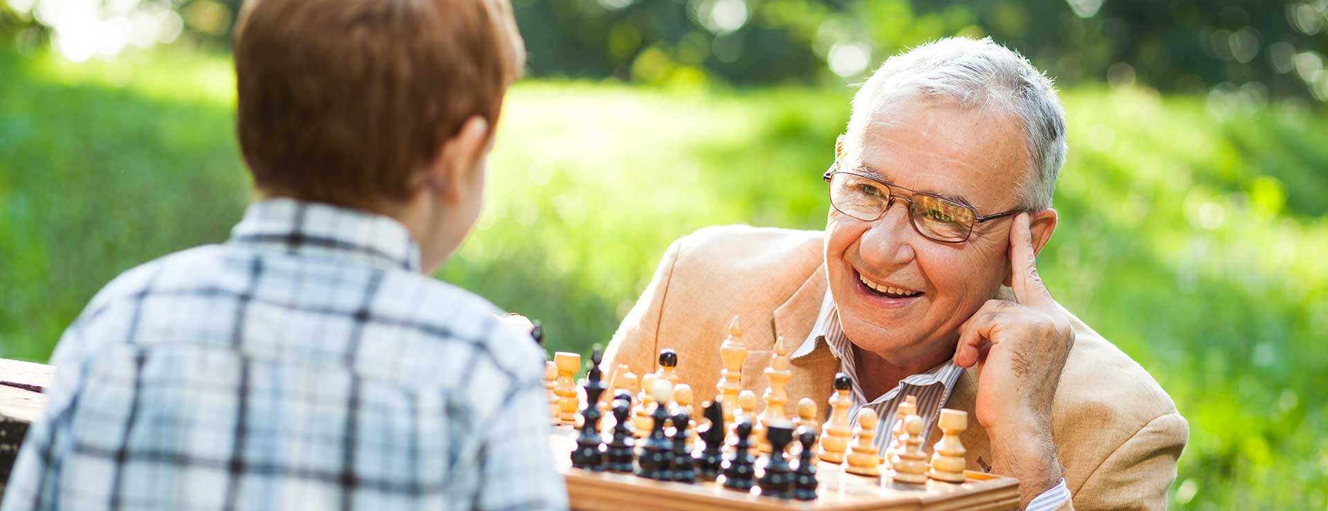 senior man plays chess with child