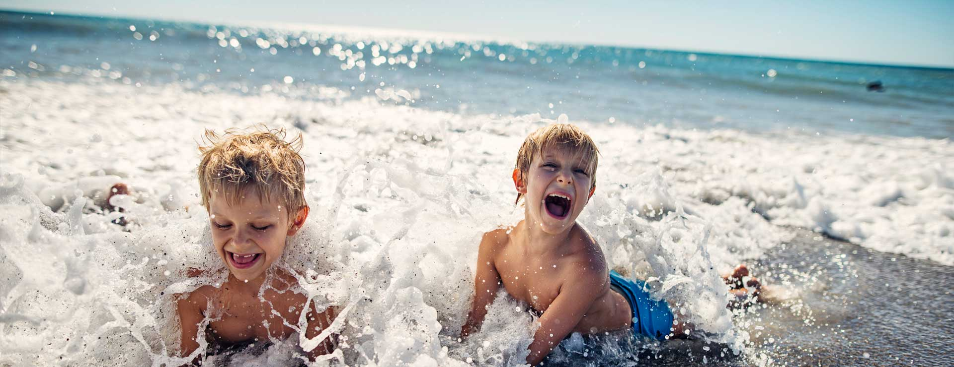 Two young boys play in the ocean waves.