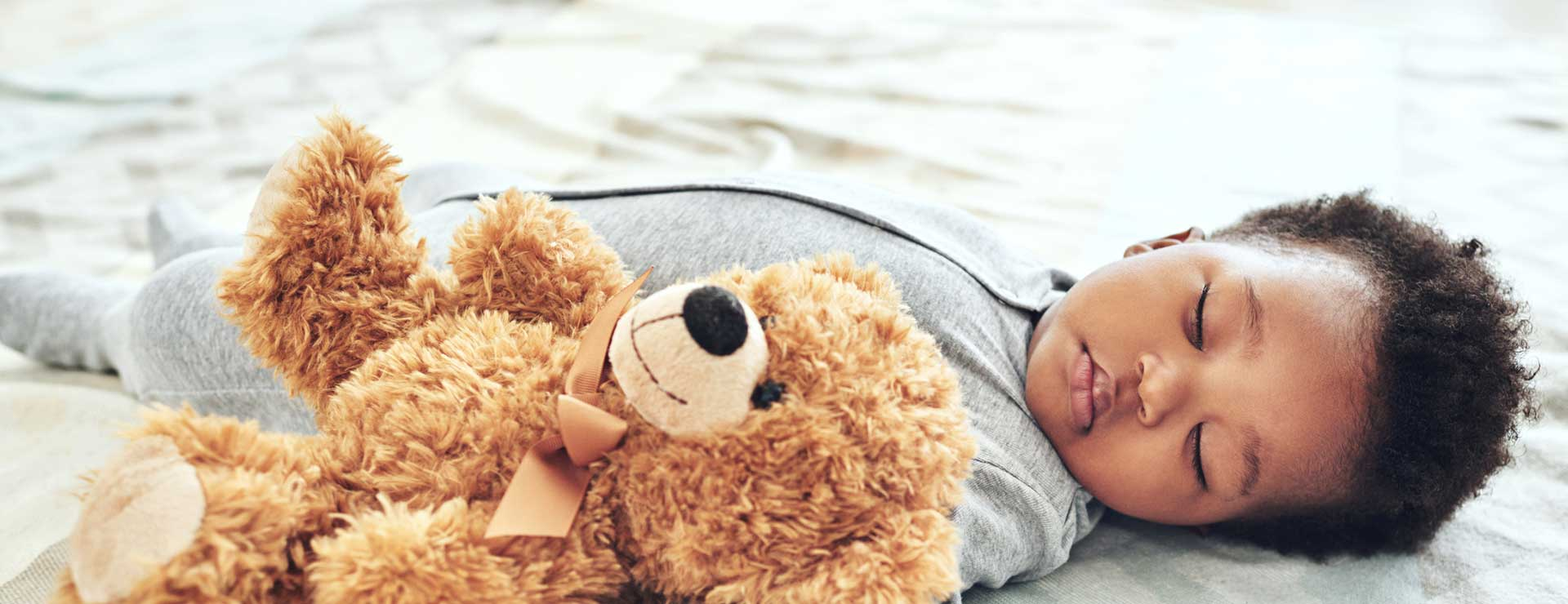 a baby sleeps in bed with teddy bear