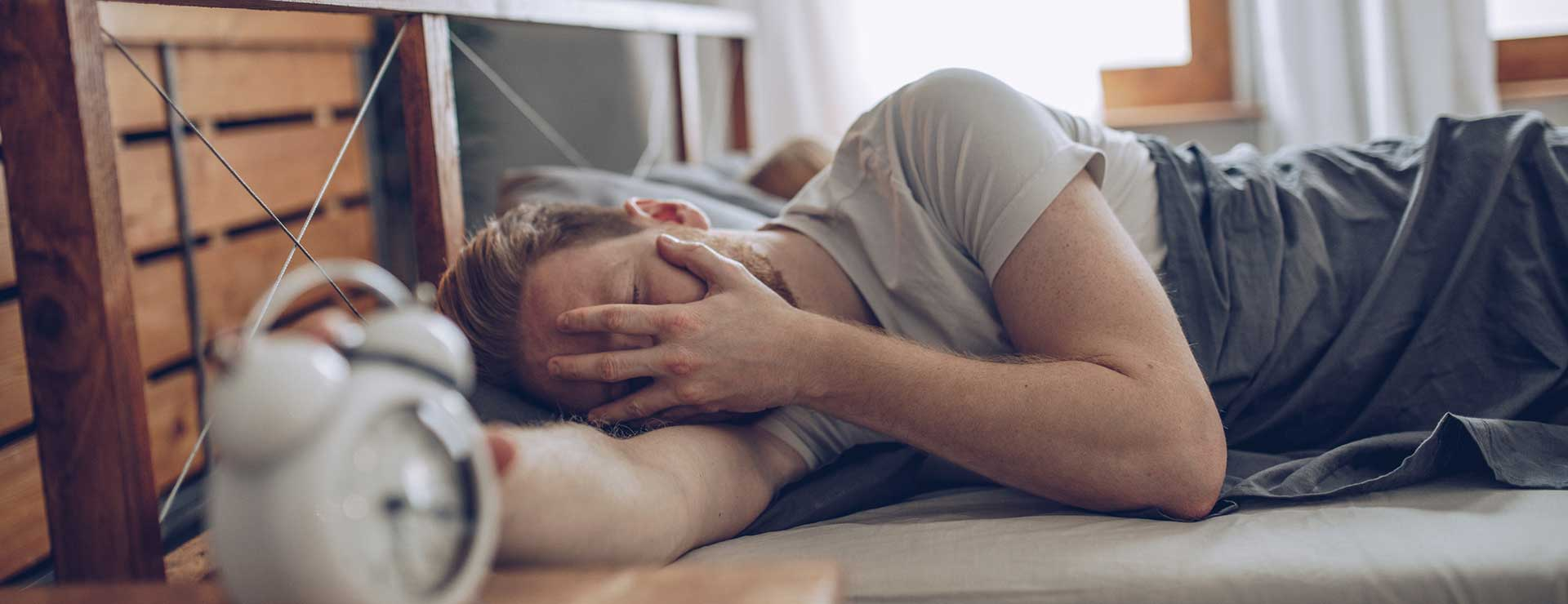 Man reaching for alarm clock while waking up