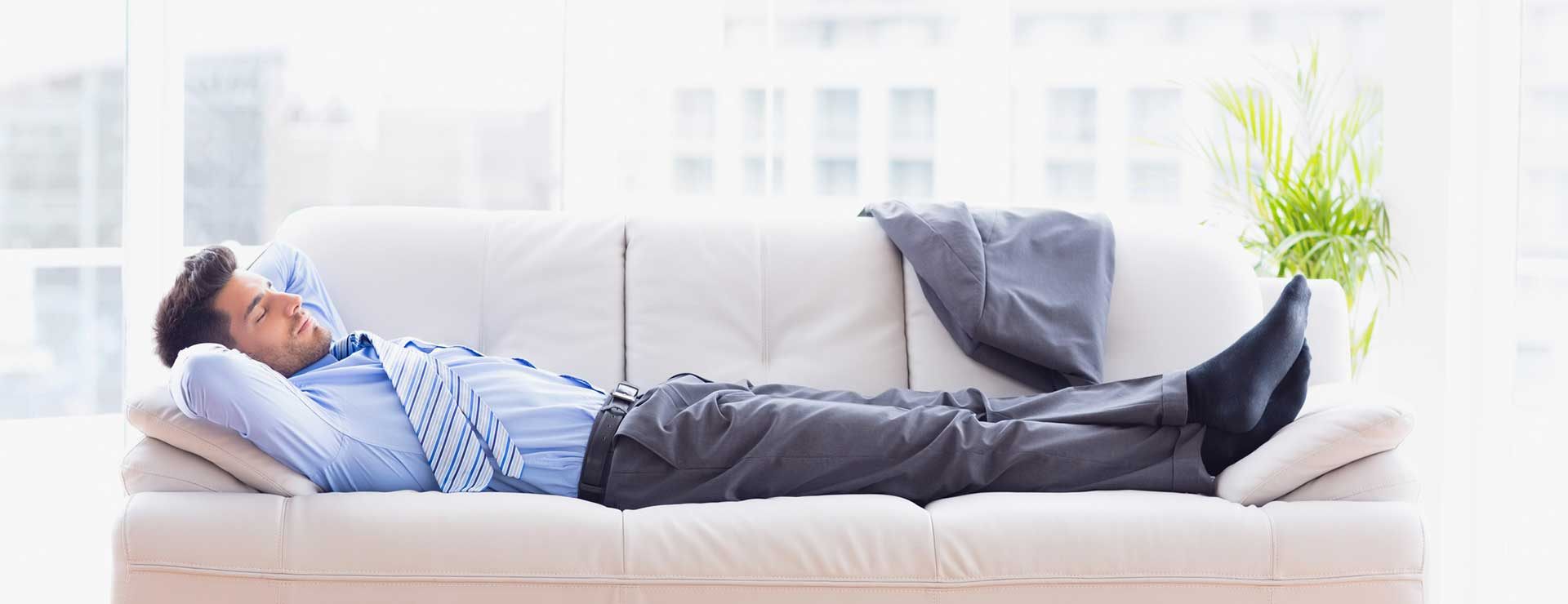 Tired business man sleeps on sofa in work clothes