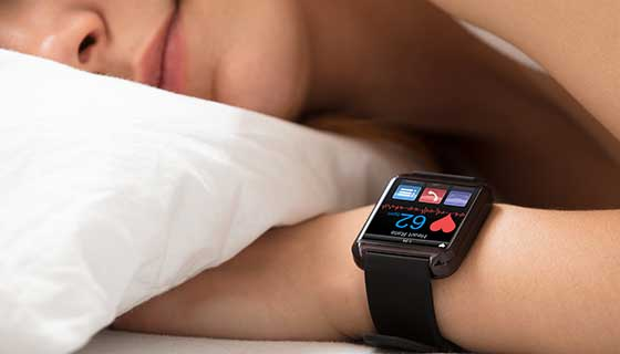A person sleeping with a smart watch tracking their sleep