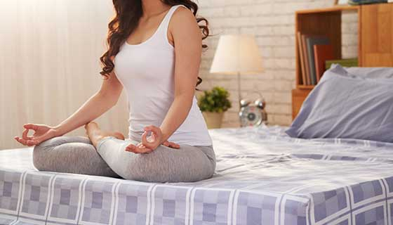 Woman sitting on her bed in a yoga pose