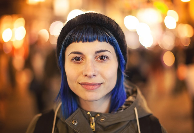 young woman with blue hair and beanie at foreground, lights out of focus in background.