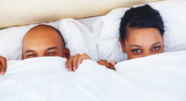 Couple peeking out from under sheets