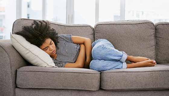 Woman laying on the couch with stomach cramps