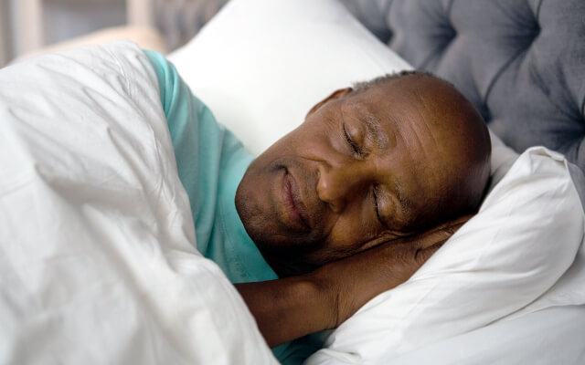 A senior man sleeps peacefully.