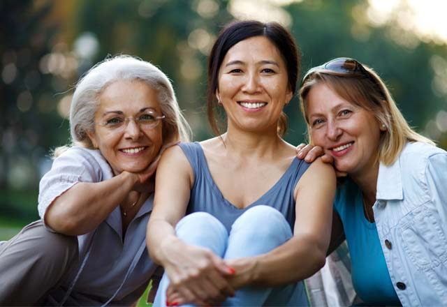 Three women of differing ages smiling