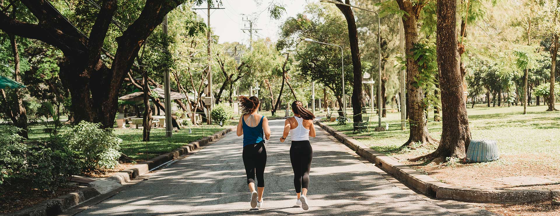 Two women jog together through a park.