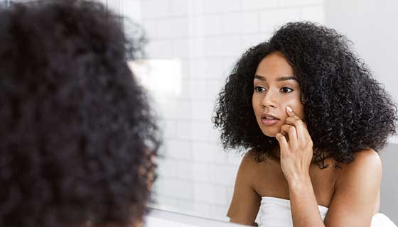 A young woman examining her face in a mirror