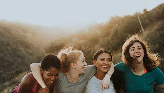 A group of female friends smile outside.