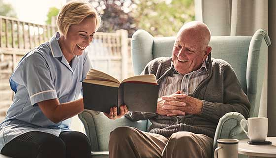 A caregiver reads to a senior man.