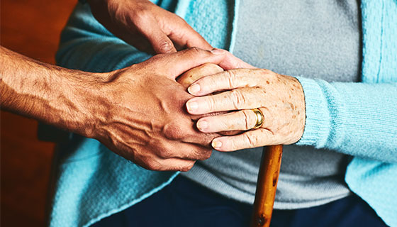 hands helping a woman with a cane
