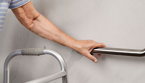 hand using a walker and safety railing teaser