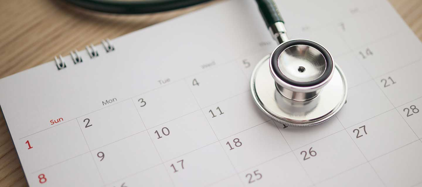 stethoscope sitting atop a monthly calendar