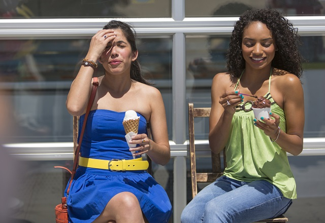 Two young women eating ice cream; one touching her painful head