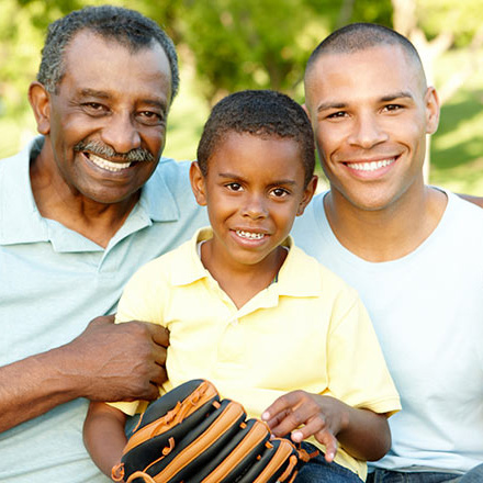 Child with a baseball glove sitting with his father and grandfather, smiling for the camera