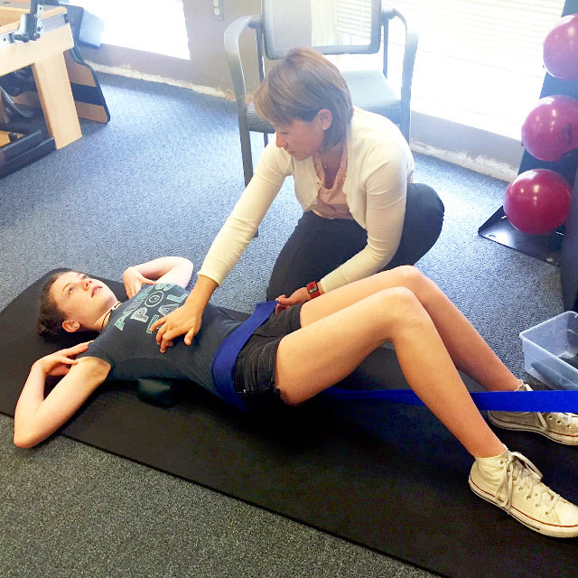 Peiting Lien with patient Sophie, helping her with scoliosis exercises