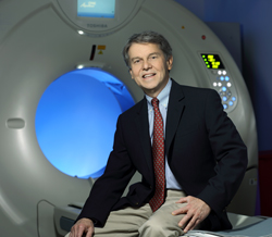 A doctor sitting next to a CT scanner