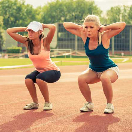 two women outside doing squats