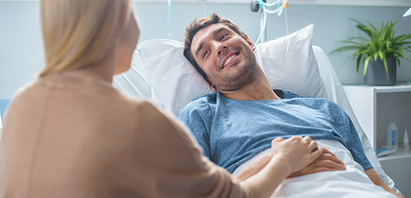 man in hospital bed smiling at woman