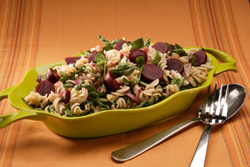 Beet and pasta salad in a colorful serving dish.