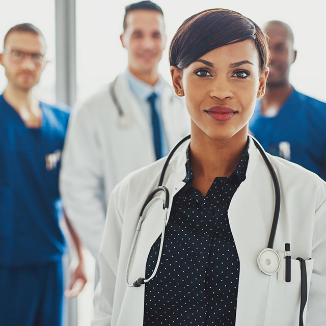 Confident doctor standing in front of her team