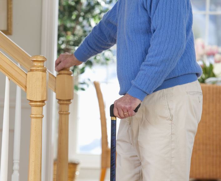 older man holding onto a stair rail