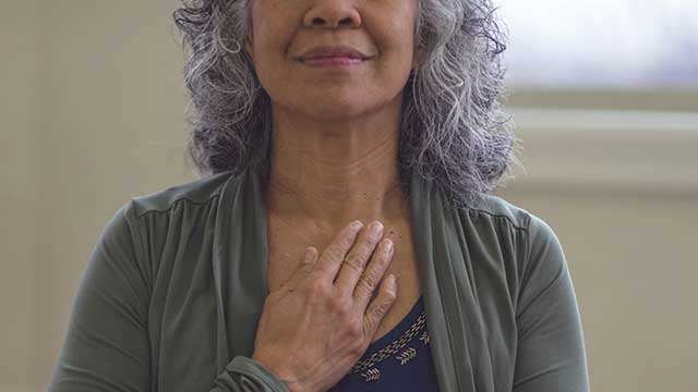 Woman taking a deep breath, with her hand on her chest
