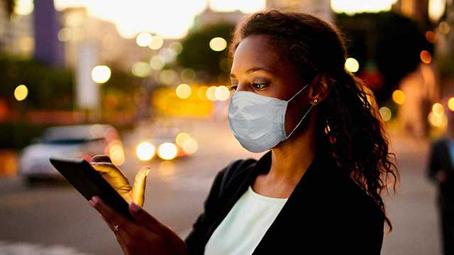 Woman reading a smartphone while wearing a mask