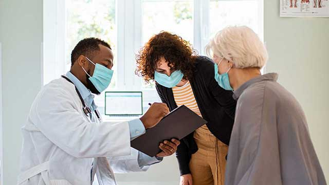 Doctor speaking with a patient and his wife.