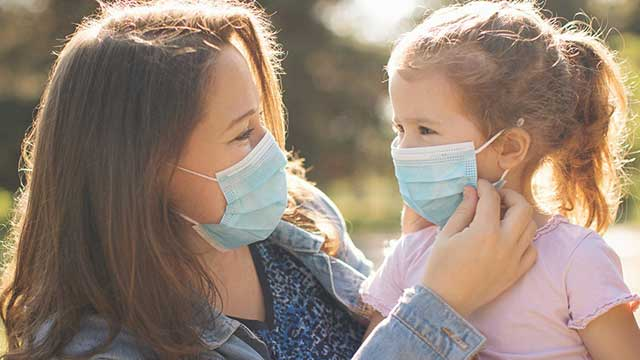 Mom and daughter wearing masks together outside