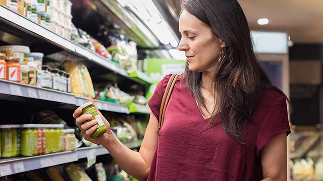 Woman browsing items in a grocery aisle