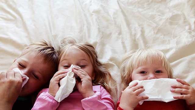 Three siblings with tissues