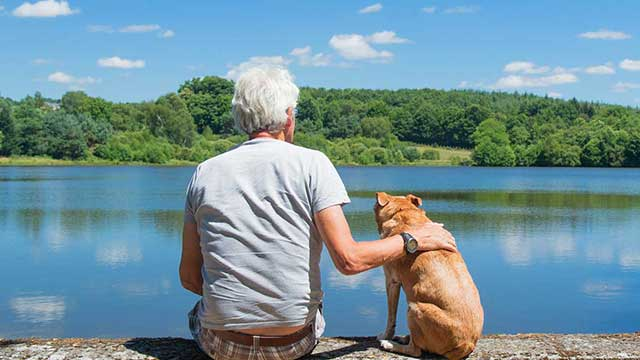 Man sitting on a dock with his golden retriever