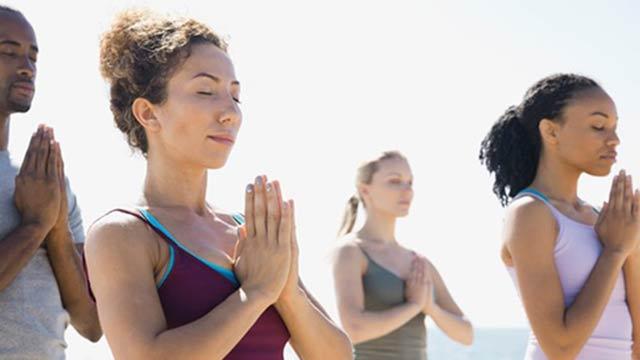 Four adults doing yoga on a sunny beach