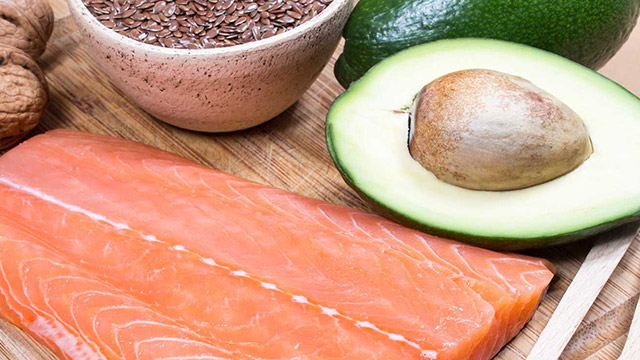 Salmon, avocado, walnuts and flax seeds on a wooden cutting board.