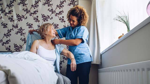 Caregiver helping woman get out of bed
